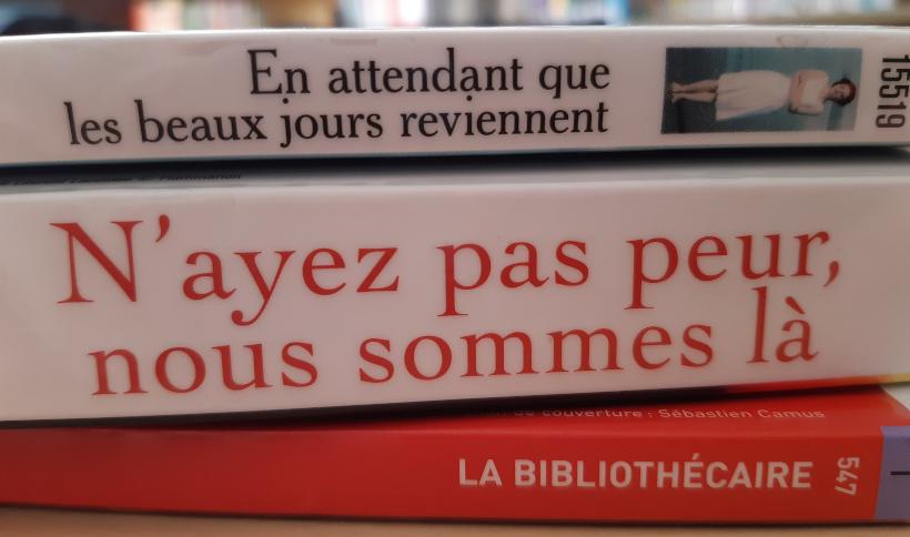 """photo d'une pile de livres formant une tranche poétique et portant le message : """"en attendant que les beaux jours reviennent ; n'ayez pas peur, nous sommes là ; la bibliothécaire"""""""